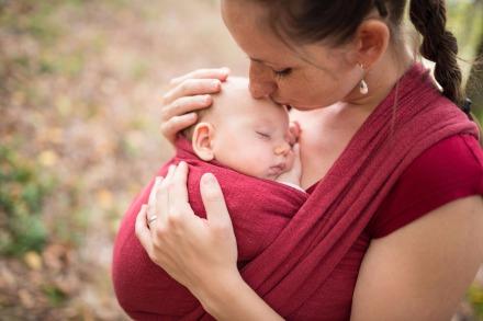 Mutter trägt ihr Baby im Tragetuch
