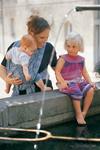 Mama mit Baby im Tragetuch und Kleinkind am Brunnen (Didymos)
