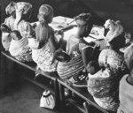 Afrikanische Frauen arbeiten mit Baby im Tragetuch (Didymos)